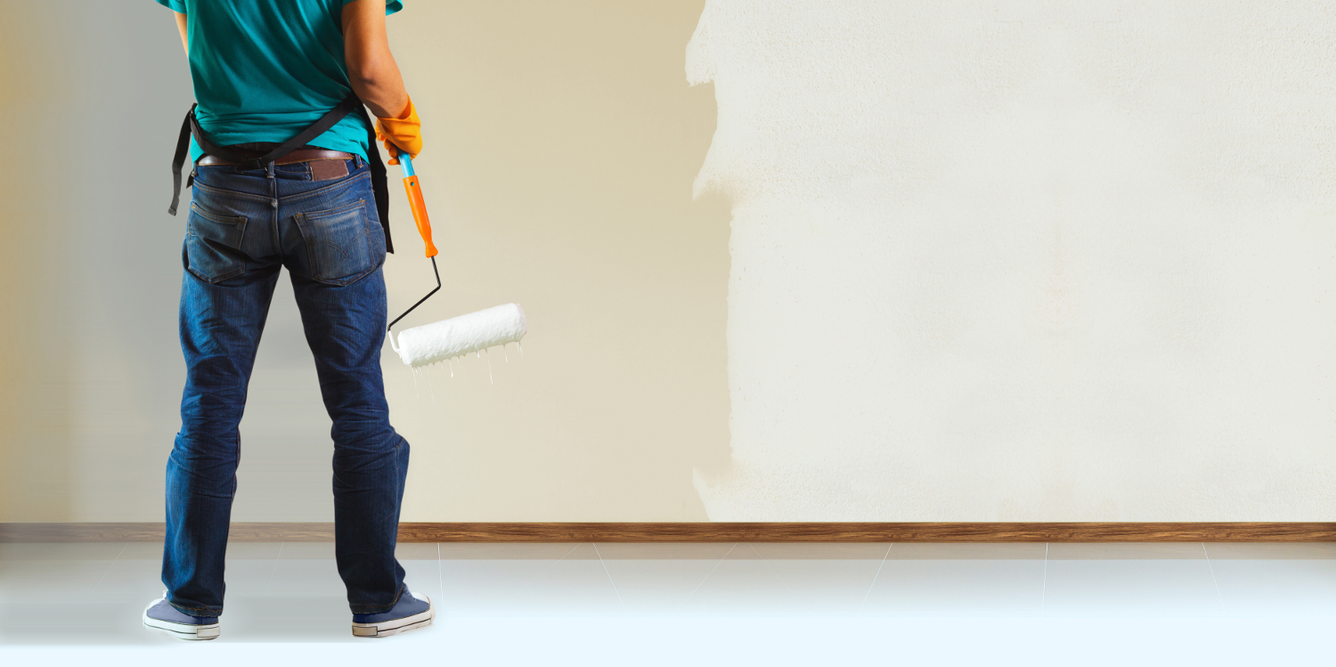 Painter painting the walls white in house
